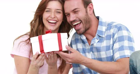 kutluyor : Smiling man offering gift to his girlfriend on white background