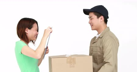 kutu : Happy delivery man delivering cardboard box on white background Stok Video