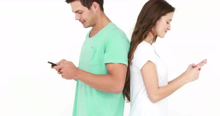 zakochana para : Couple standing back to back and texting on white background