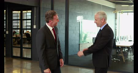 tratar : Businessmen handshaking and talking in office