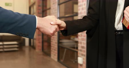 advokát : Mid view of a businessman shaking hand of his lawyer in office