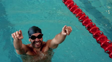 atleta : Fit man raising arms in the pool at the leisure centre