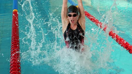 atlet : Fit woman raising arms in the pool at the leisure centre Stok Video