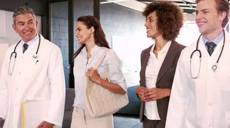 сотрудники : Doctors and businesswomen walking and talking together at hospital