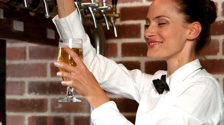 beer tap : Barmaid pulling a glass of beer in bar Stock Footage
