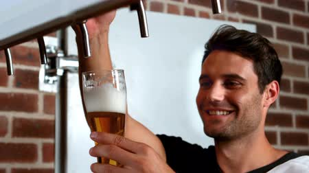 musluk : Smiling barman pulling a pint of beer in bar Stok Video