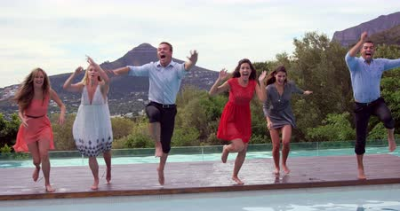 salto : Group of friends jumping in swimming pool in slow motion
