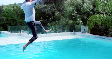 biznesmeni : Businessman jumping in the swimming pool in slow motion