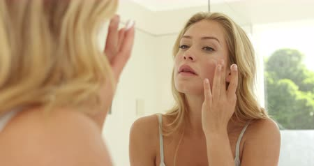 krém : Young woman applying cream on her face in the bathroom Dostupné videozáznamy