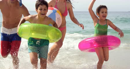 Happy family running in water on the beach