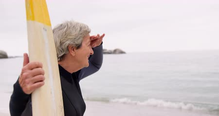 серфер : Retired woman holding a surfboard on the beach in slow motion Стоковые видеозаписи