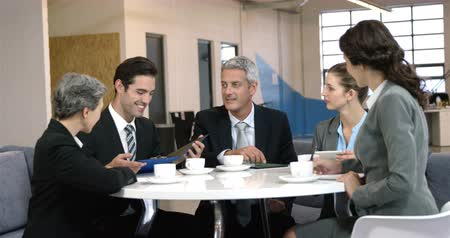 встреча : Business people drinking coffee during a meeting