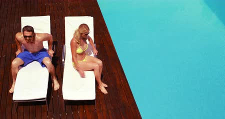 tonları : Happy couple going lying on deck chairs poolside Stok Video
