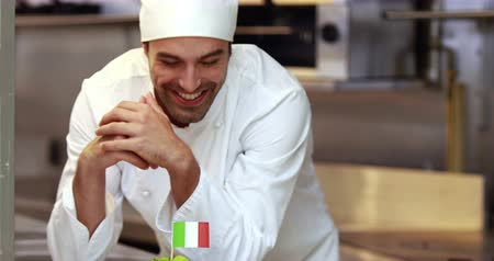 specialties : Handsome chef putting Italian flag on dish in the kitchen
