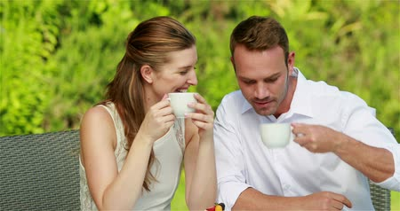 fresh coffee : Sweet couple drinking coffee in the restaurant garden Stock Footage