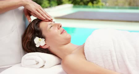 shiatsu : Woman getting a face massage by beauty therapist next to the pool Stock Footage