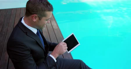 poça de água : Businessman using tablet computer by the pool