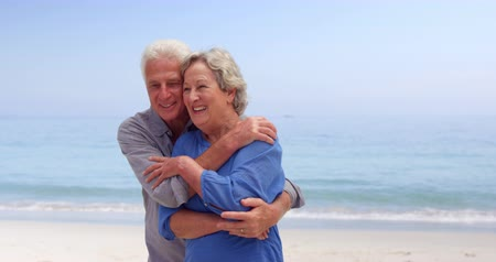 párosít : Old couple hugging and dancing at the beach