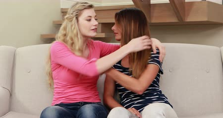 друзья : Blonde comforting her crying friend on the sofa