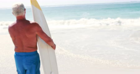 surf : Rear view of old retired man going to the beach while holding surfboard