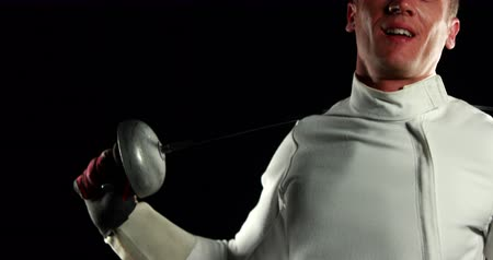 meç : Sportsman practices fencing and stretches on black background