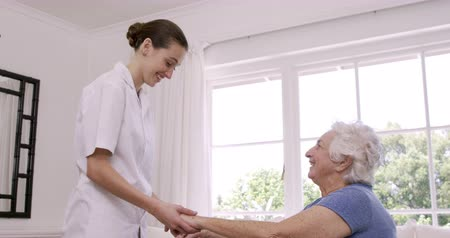home life : Smiling nurse helping senior woman doing exercises at home