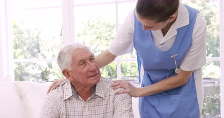 guy home : Nurse talking to senior man at home Stock Footage