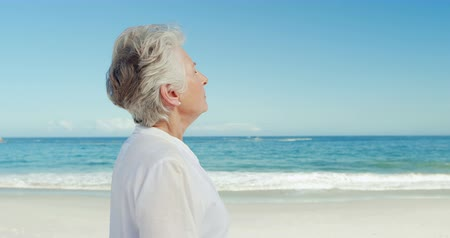 serene : Senior woman relaxing on the beach Stock Footage