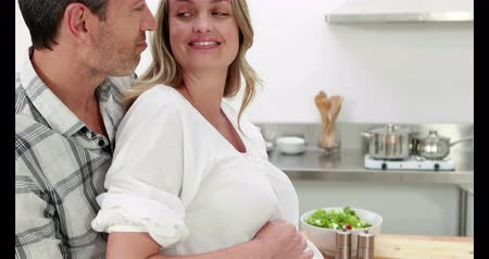 terhes : Pregnant woman making a salad with her husband in the kitchen