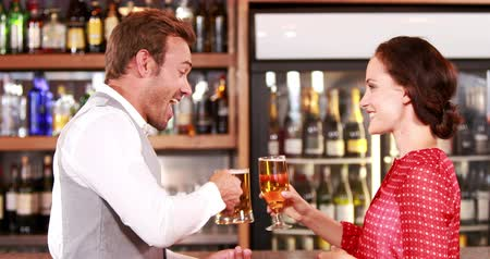 паб : Smiling couple talking and toasting together at bar