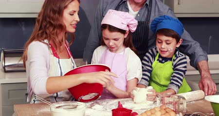 развлекать : Happy family cooking biscuits together in the kitchen