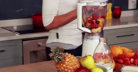 kalcium : Happy woman making smoothie in the kitchen