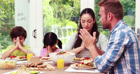 dua eden : Family praying before eating lunch at home Stok Video