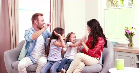 kanapa : Happy family raising arms and high fiving at home Wideo