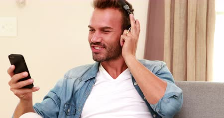 dokunaklı : Handsome man listening to music, singing and using smartphone on the sofa