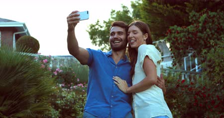 carinho : Happy couple taking selfie in the garden in a sunny day
