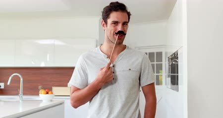 bigodes : Handsome man with fake mustaches making faces in the kitchen