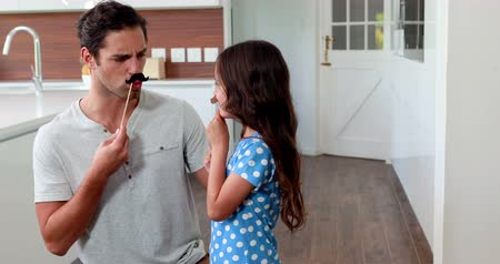 bigodes : Father and daughter with fake mustaches making faces in the kitchen