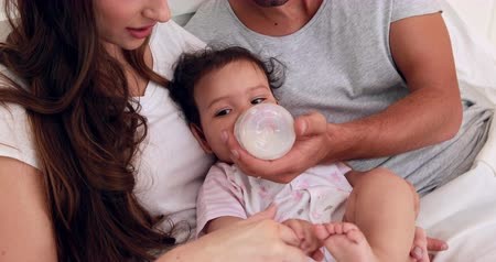 feed on : Loving parents feeding their baby on the bed Stock Footage
