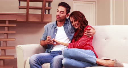 lounge : Young couple embracing on sofa in living room