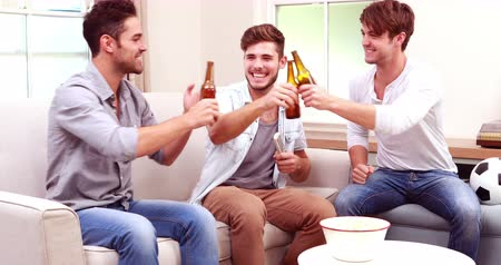torcendo : Friends watching sport on tv and drinking beer on sofa Stock Footage