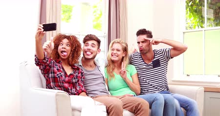 képek : Happy friends taking selfie on the sofa at home