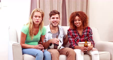 beer house : Smiling friends watching tv while eating popcorn and drinking beer at home