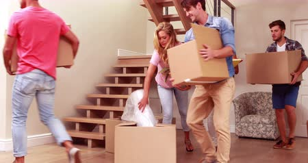 home life : Smiling friends moving boxes together at new home