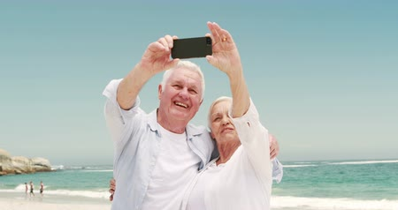 senior lifestyle : Old retired couple taking selfie together on the beach Stock Footage