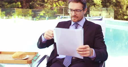 verifying : Handsome businessman drinking coffee and reading documents poolside Stock Footage
