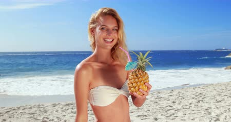 ananász : Attractive blonde drinking cocktail in pineapple at the beach Stock mozgókép