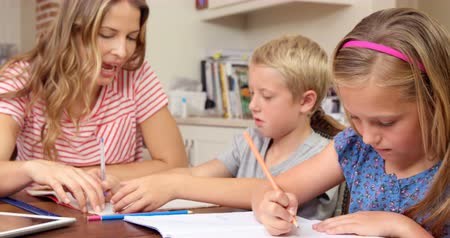 домашнее задание : Mother helping children doing homework at home
