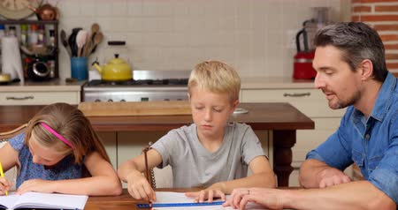 домашнее задание : Parents helping children doing homework at home Стоковые видеозаписи