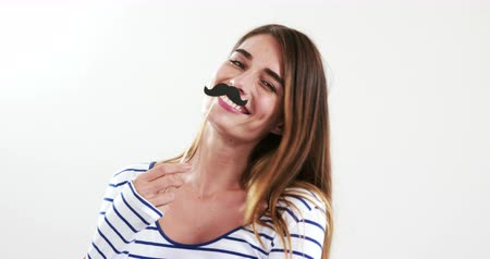 bigodes : Pretty brunette with fake mustache posing for camera on white screen Stock Footage